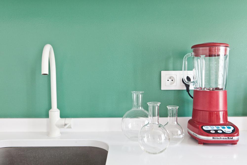 Frontal de la cocina en verde que contrasta con la batidora roja.