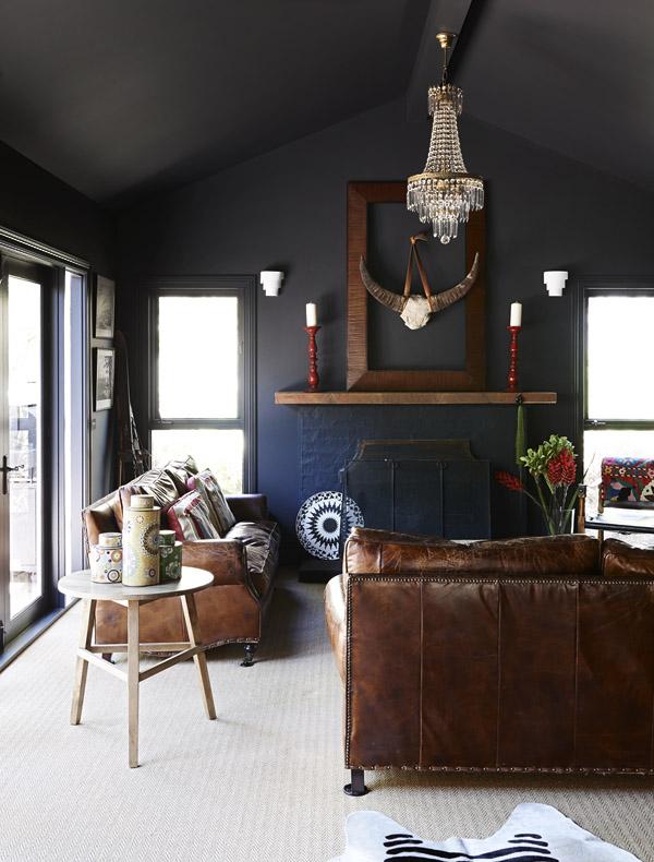 Una zona de estar con el color oscuro de la pared y el suelo cubierto con una alfombra de sisal a modo de moqueta.