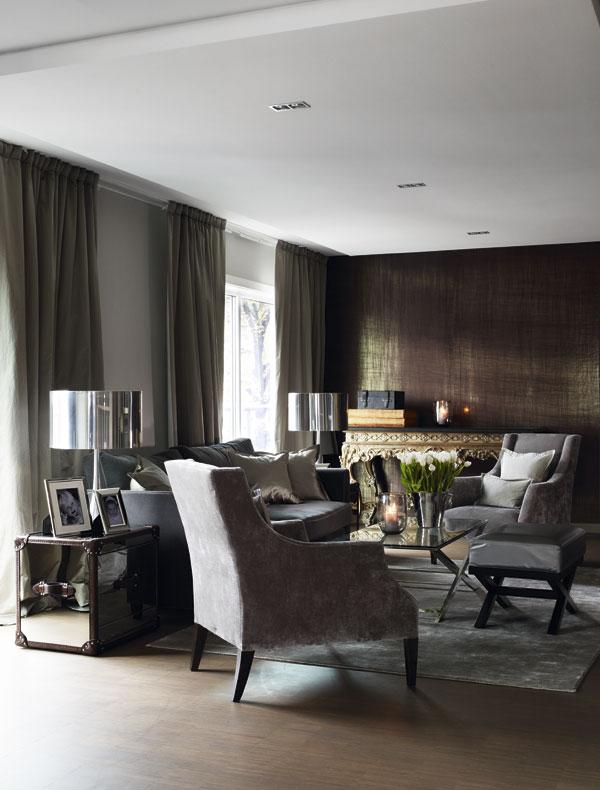 En el salón se mezclan elementos de diferentes matices de gris. el revestimiento de la pared del fondo es precioso.