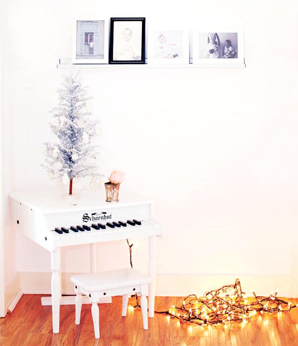 Rincón decorado con piano, arbolito de Navidad  y guirnalda de luces.