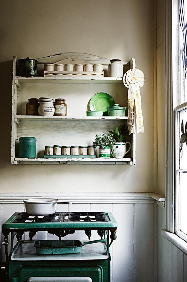 Estantería en la cocina de estilo antiguo, con vajilla desparejada en tonos de verde.