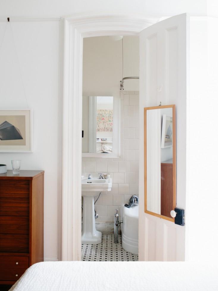 Entrada al baño, revestido con la baldosa tipo metro biselada en blanco.