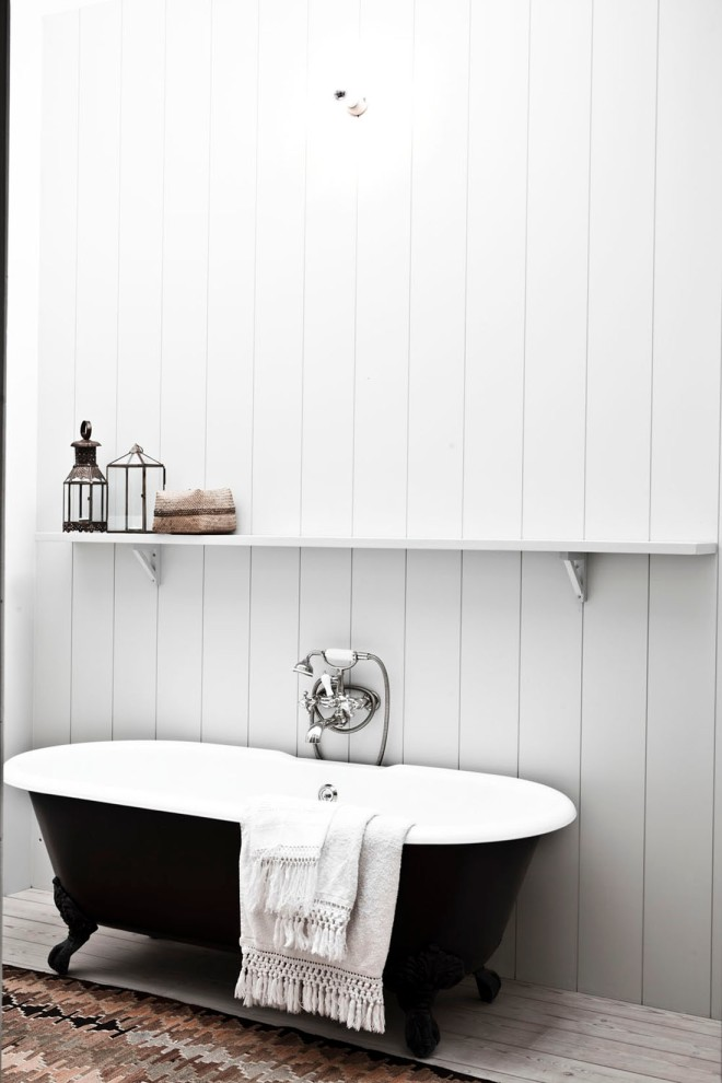 Bañera exenta en el baño revestido de madera.