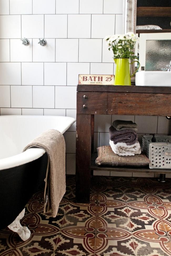 Vista del baño donde han reciclado todo, desde el suelo de baldosa hidráulica hasta el mueble del lavabo. Me gusta la disposición de los azulejos cuadrados.