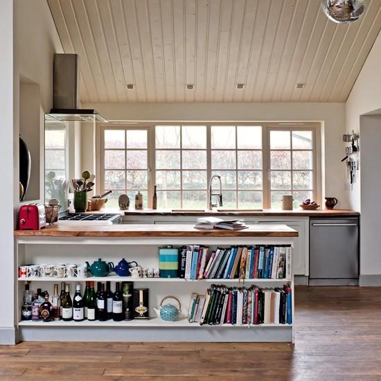 La cocina está abierta al comedor;  hacia este lado del comedor tiene estantes con libros y botellas.