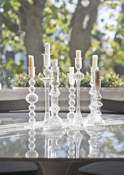 Preciosos candelabros de vidrio en la repisa de la ventana
