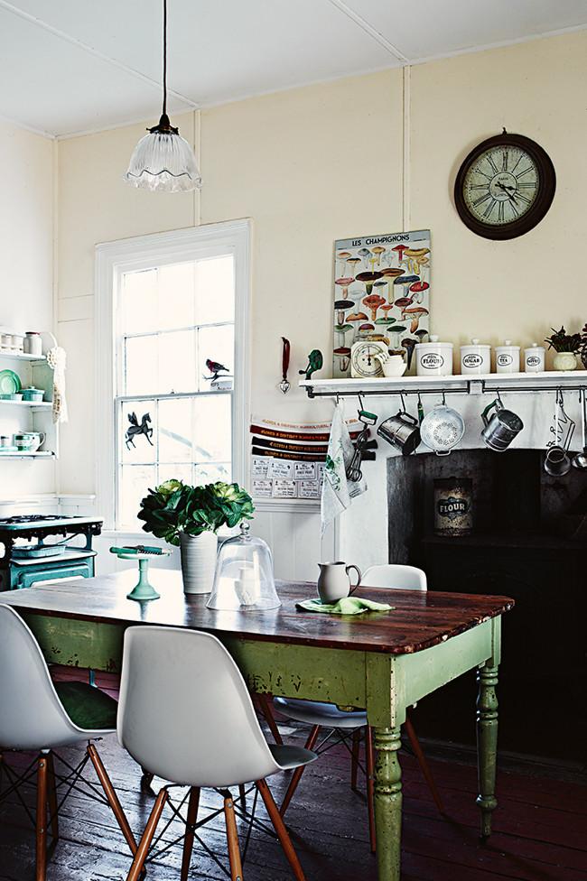 Zona de comedor en la cocina. las sillas de los Eames contrastan con la mesa,  chimenea y objetos decorativos más antiguos.