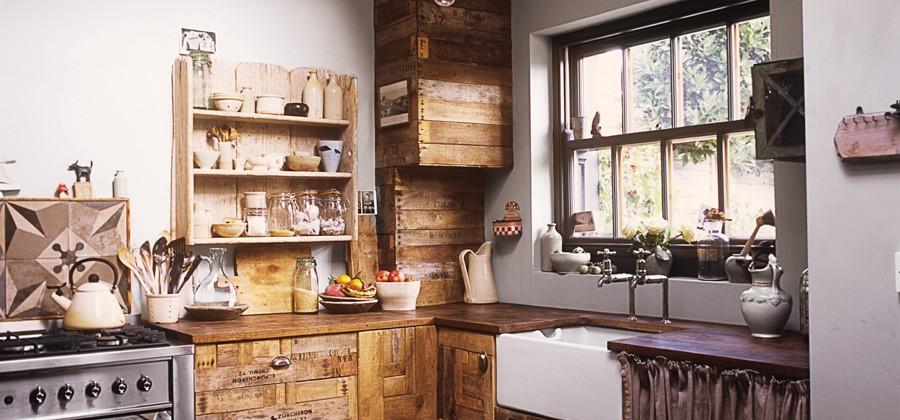 La cocina está fabricada con madera reutilizada, conformando los muebles, estanterías, etc... Me encanta el armarito cerrado con una cortina!