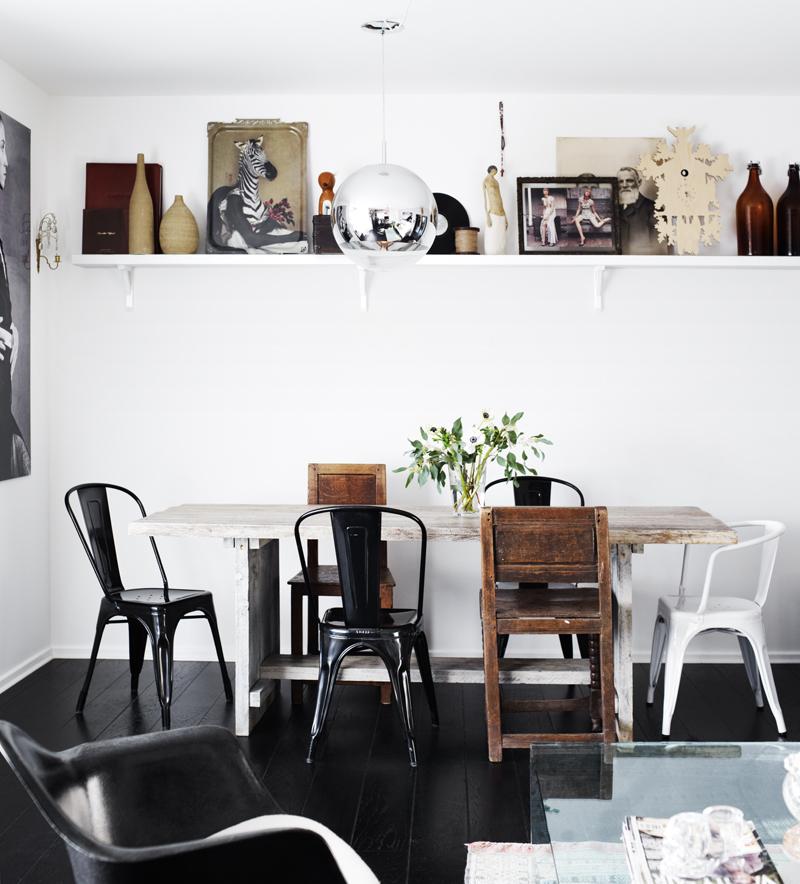 Comedor con diferentes modelos de silla, estante con cuadros apoyados La  lámpara se confunde por su superficie pulida.