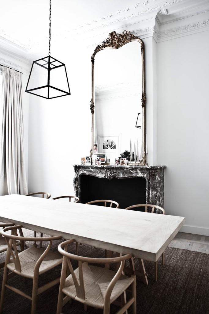 Vista del comedor que mezcla lo clásico del espacio, como la preciosa chimenea de mármol original y el increíble espejo de marco dorado con la mesa de diseño más recto y las sillas Wishbone de Wegner.