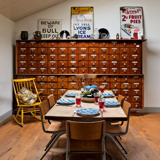 En el comedor, un mueble clasificador con mesa y sillas de escuela.