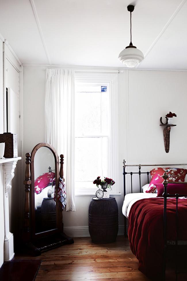 Dormitorio con cama de forja y chimenea de mármol.