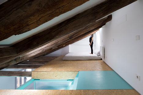 En el altillo se encuentra la cama y la bañera empotrada. Al lado de la bañera hay dos puertas que se abren y que contienen  zona de almacenaje y un tocador.