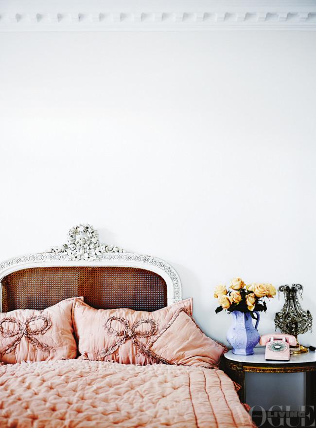 Dormitorio con cabecero de anea, cojines y cubrecama rosa