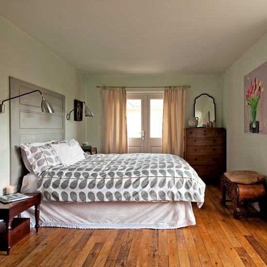La cama del dormitorio principal tiene como cabecero una puerta pintada en gris verdoso.