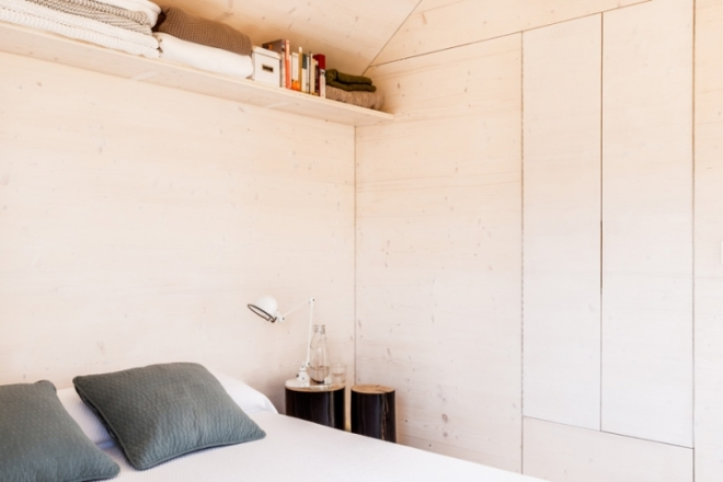 Dormitorio con el estante que recorre toda la vivienda.