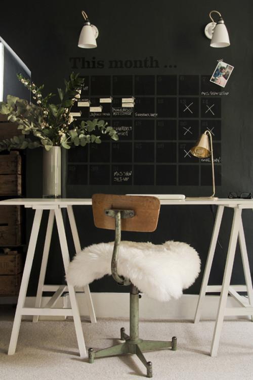 Estudio con mesa sobre caballetes y calendario de pizarra negra sobre pared gris oscura.