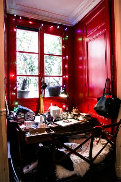 Estudio pintado en rojo y con unas alegres luces rodeando la ventana.