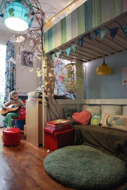 Habitación infantil con litera y zona de juegos.