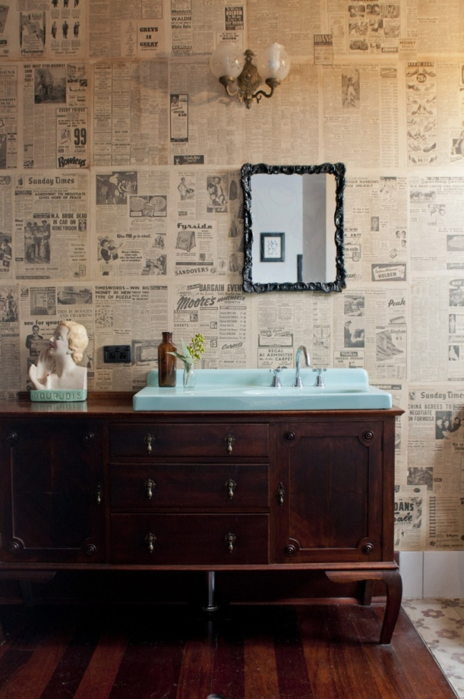 En el baño han reciclado un aparador antiguo como mueble de lavabo. Me gusta el efecto que hace el papel de periódico con el espejo.
