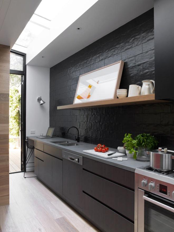 Cocina en tonos grises oscuros combinados con madera de roble blanqueada. En el suelo continua el mismo parquet que en el resto de la vivienda.
