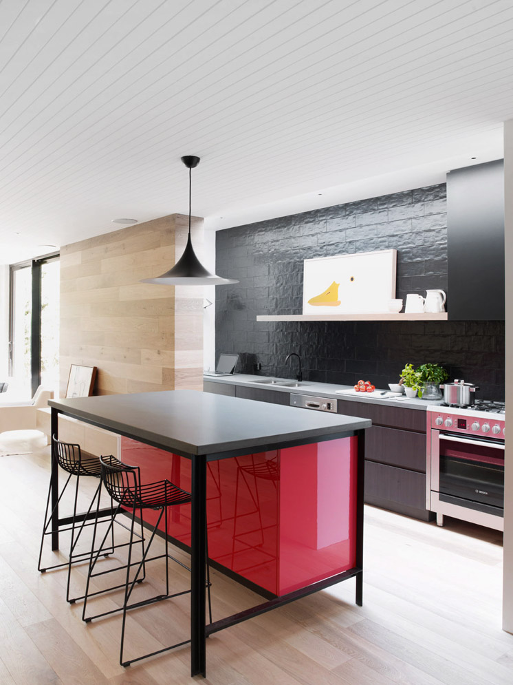 Integración de cocina con estar por medio de los materiales, al estar la pared revestida con el mismo roble que aparece en algunas de las piezas de la cocina.
