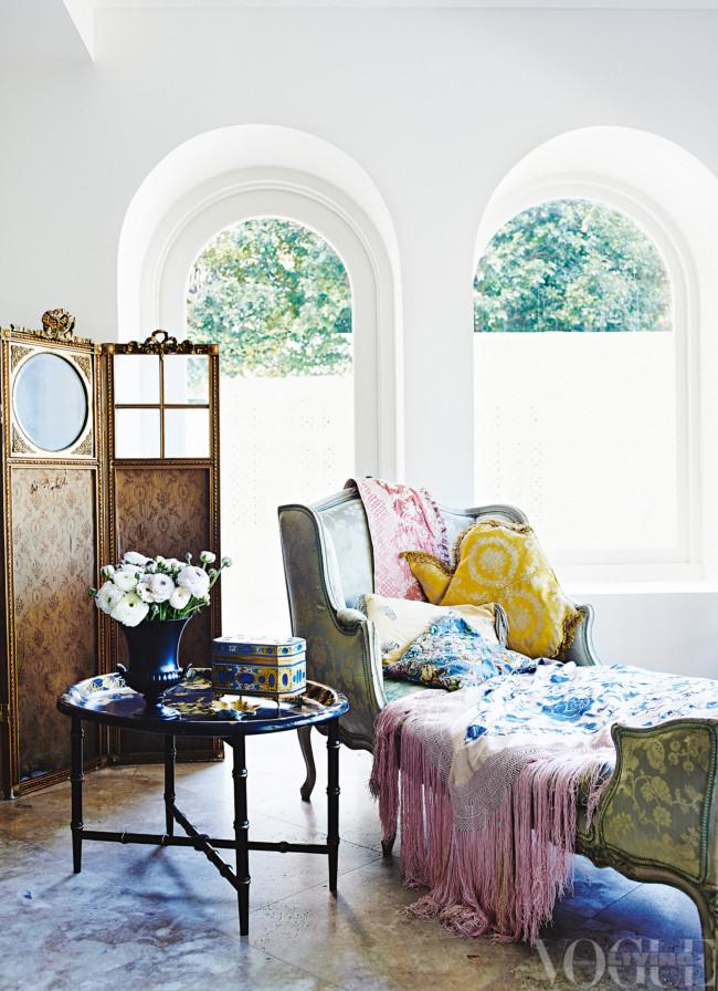 Zona de lectura con biombo de aire oriental, mesa y chaise longue cubierto de una manta y cojines de colores.