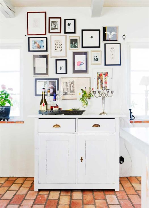 Precioso detalle de decoración con cuadros en la cocina. Componen muy bien un espacio de almacenaje dentro de la cocina comedor.