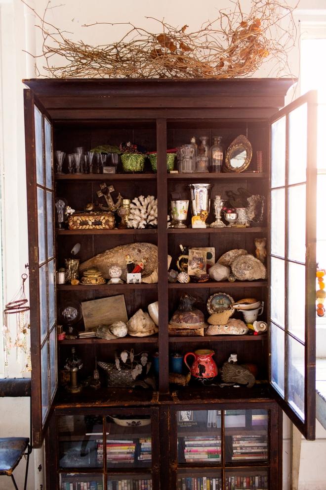 Armario alacena lleno de elementos, piedras, juguetes.