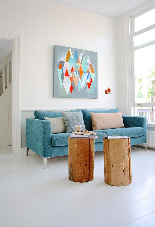 El sofá azul encaja perfectamente con el cuadro y cojines, creando una composición alegre.