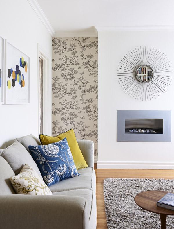 Zona de estar con un maravilloso espejo de sol, una chimenea encastrada en la pared y un papel pintado en la esquina que da su toque a este espacio de elementos sobrios.