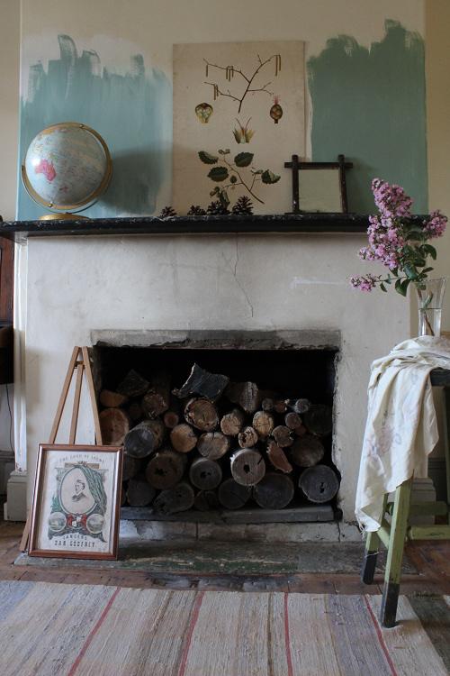 Chimenea encalada con remates en madera tosca, preciosa con los elementos decorativos que ha incluido, el cuadro, el globo terráqueo.