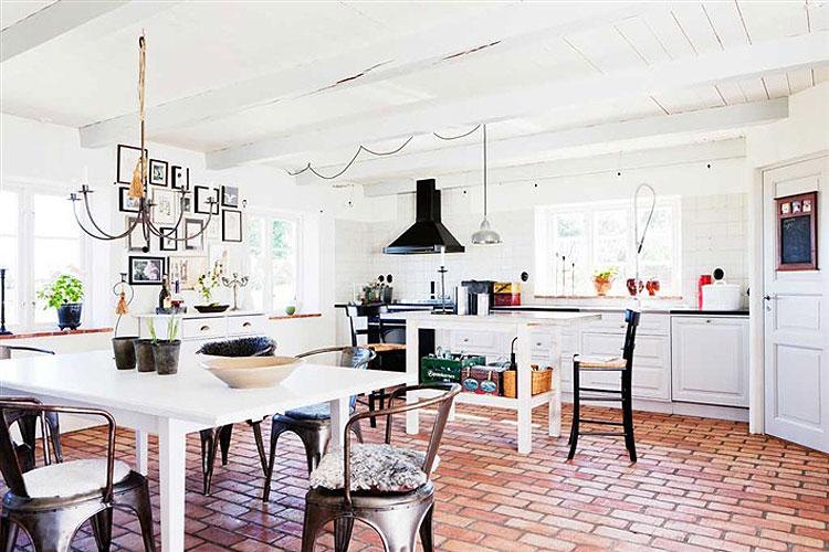 El precioso espacio que han conseguido en la cocina comedor destaca por el uso del barro cocido como revestimiento, las vigas vistas y pintadas de blanco y la decoración poco habitual de este espacio. Me encantan los cuadros en la cocina!