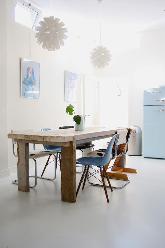 Comedor abierto en la cocina.  La mesa de madera maciza y las sillas diferentes quedan genial. La trona de Stokke es ya un icono del diseño.