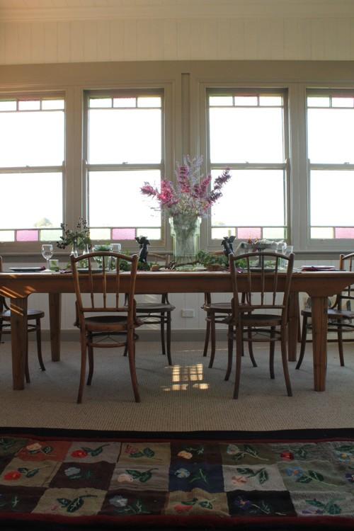 Comedor con una mesa muy grande y mucha luz que entra por las ventanas emplomadas.