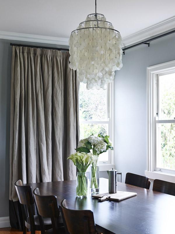 El comedor es un espacio elegante decorado con colores sobrios también. Destaca la lámpara de nácar de Panton y las impresionantes cortinas de lino (el lino en cortinas es un must!)