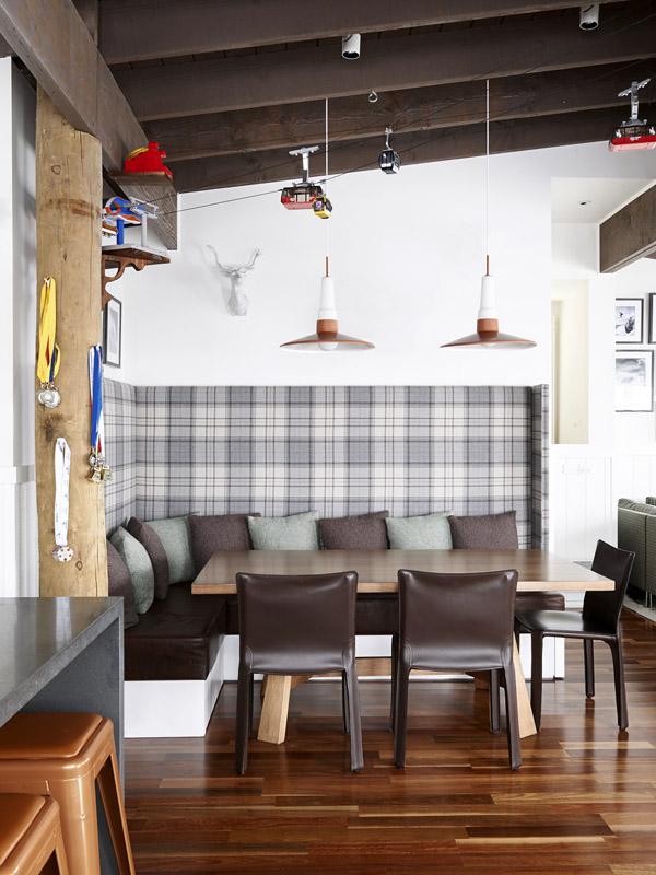 La zona de comedor se amuebla con un banco sujeto a la pared y tapizado con una preciosa tela con diseño tartan, uno de varios que veremos en esta vivienda.