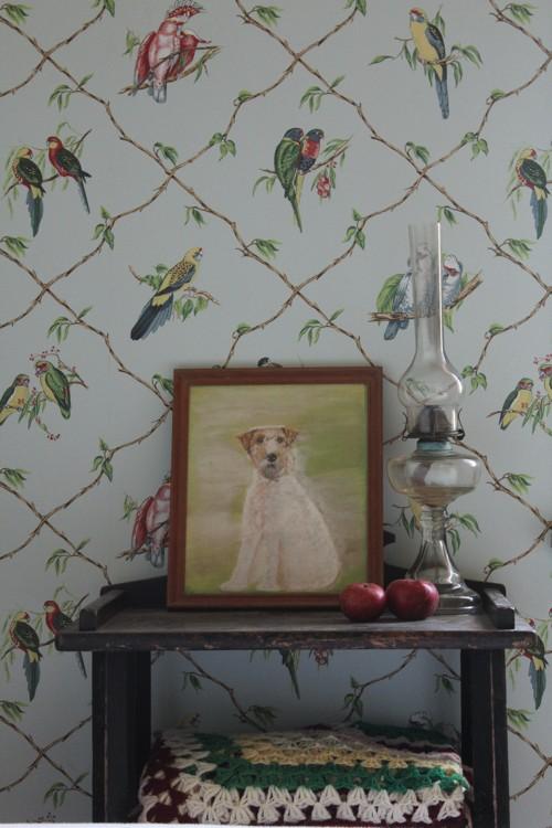 Detalle del papel pintado de pájaros y aparador rústico.