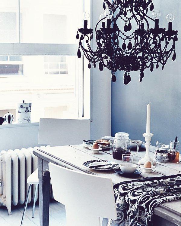 Mesa preparada para el desayuno. La lámpara de lágrimas en cristal negro contrasta con la pared en un azul grisáceo y el blanco de la mesa.