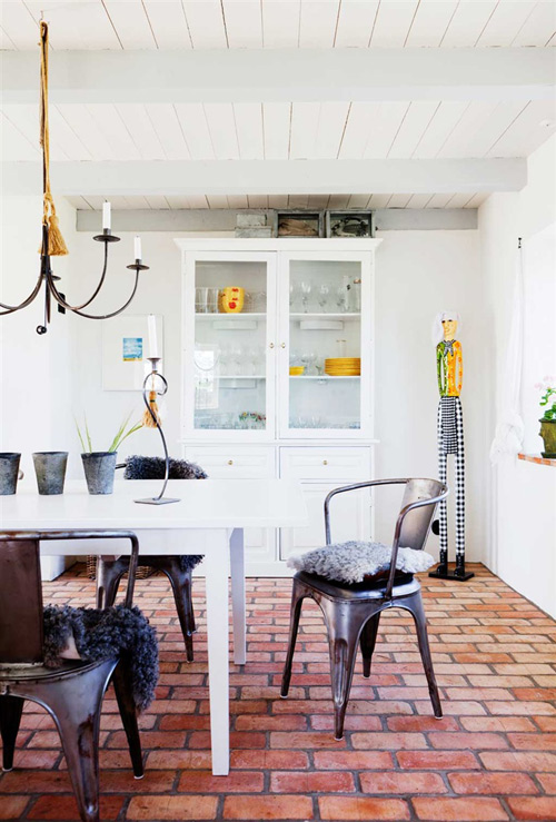 La alacena blanca con elementos amarillos da un toque de alegría al espacio del comedor, decorado con una lámpara de brazos y unas butacas Tolix de hierro.