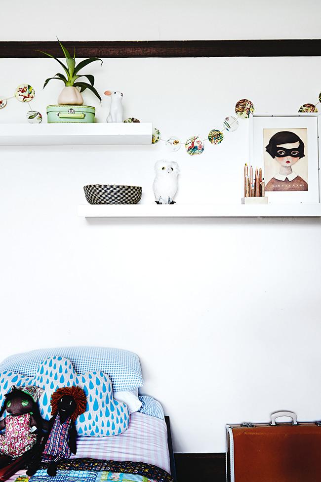 Me encanta la lámina de la chica del antifaz y los demás elementos decorativos de esta habitación infantil.