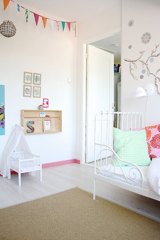 Preciosa habitación infantil de una niña con la cama de hierro forjado.