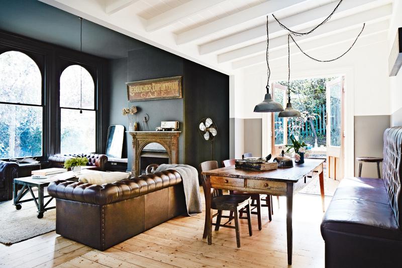 Vista de la zona de estar en la que destacan el color gris oscuro de las paredes, el precioso sofá Chester, la mesa de comedor y las lámparas de estilo industrial.