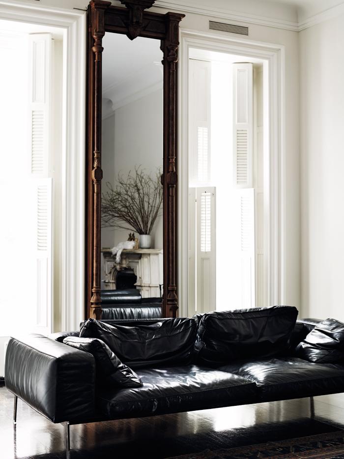El estar se ha amueblado con un sofá de Poliform de piel. El espejo es maravilloso, alto y precioso el reflejo.