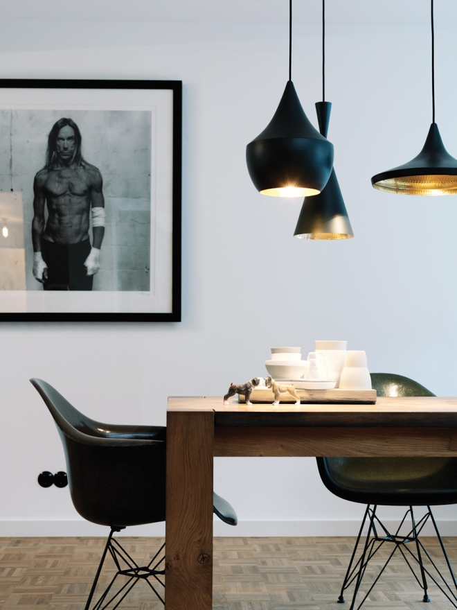 Las lámparas de Tom Dixon en primer plano junto con el perfil de la Palstic Eames Chair en butaca negra y una foto de Iggy Pop en blanco y negro, un conjunto precioso.