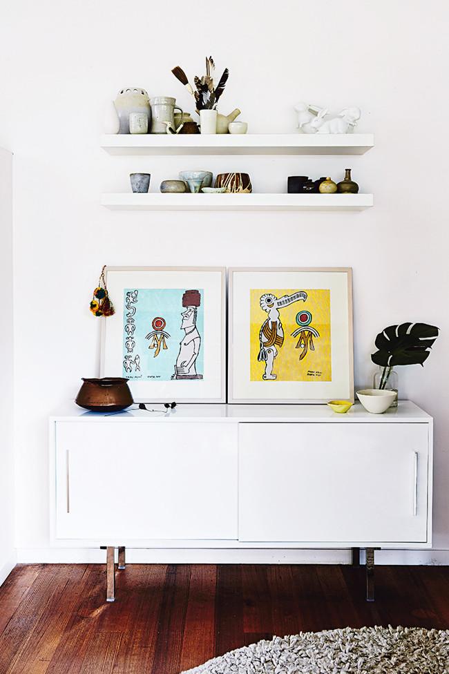 Precioso rincón compuesto de un mueble bajos, unas serigrafías y unos estantes estrechos con elementos decorativos.