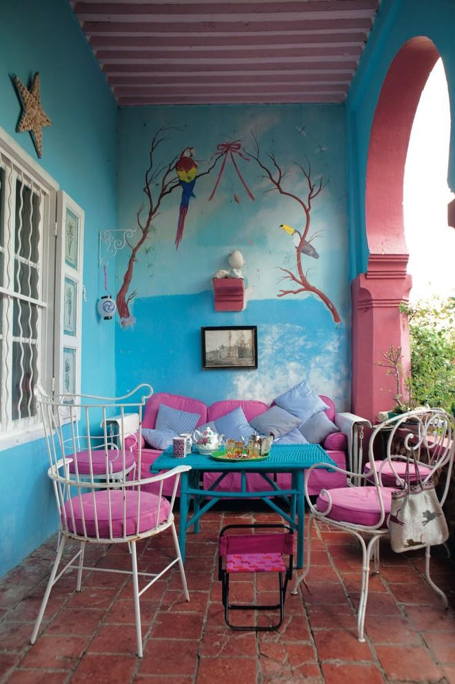 Porche con mural de colores, el azul con el rosa da mucha alegría a este rincón de la vivienda.