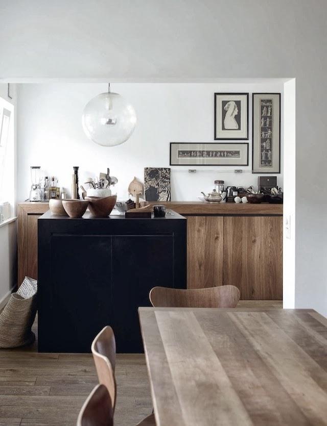 La zona de la cocina y comedor se ha decorado con mobiliario de madera de roble, elementos negros y el ambiente general en blanco. No hay ningún color que sobresalga por encima de los demás.