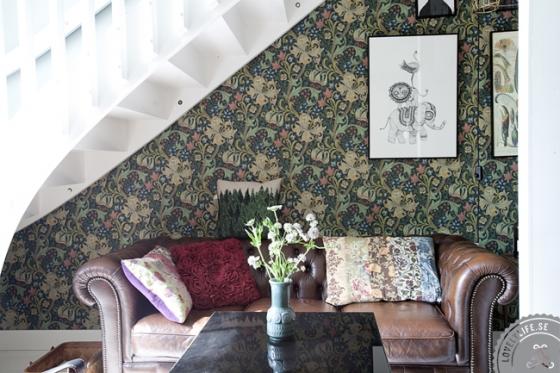 Debajo de la escalera se utiliza un papel pintado con un dibujo grande, combinado con otro tipo de telas y la piel gastada del chester.