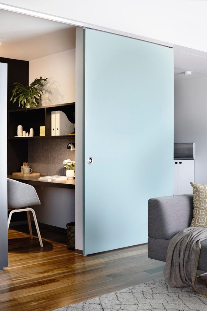 La puerta corredera que divide el estudio y la cocina del espacio del estar tiene un color muy fresco y suave.